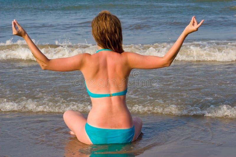 De zitting van het meisje op het strand royalty-vrije stock afbeelding