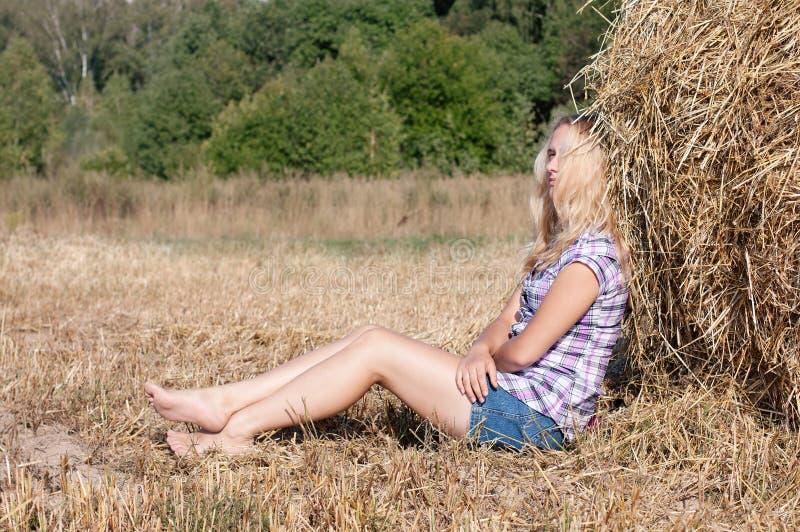 De zitting van het meisje op hooi royalty-vrije stock afbeelding