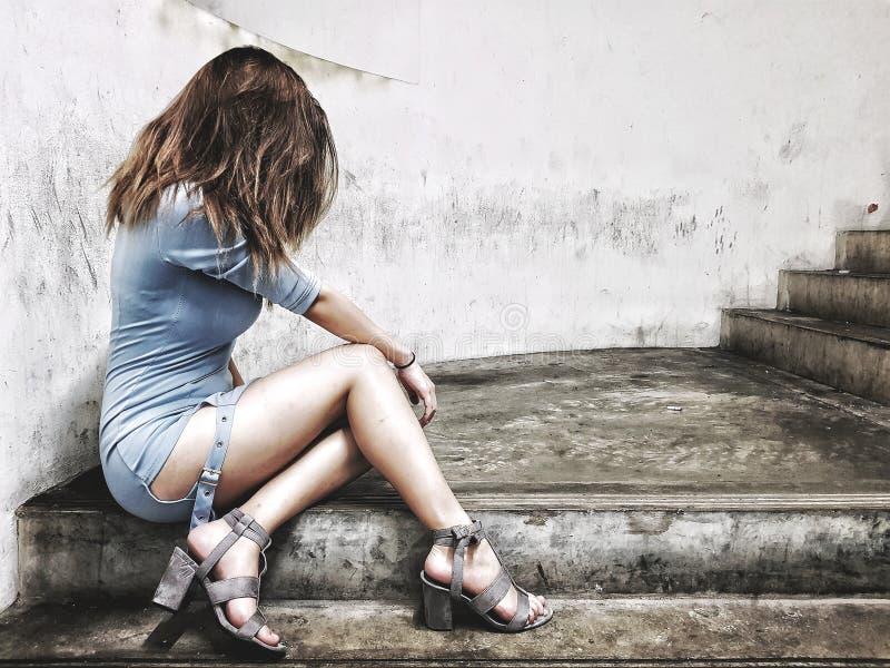 De zitting van het meisje op stappen stock foto's