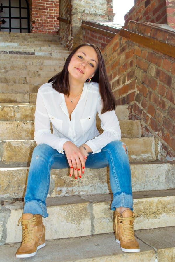 De zitting van het meisje op treden stock afbeelding