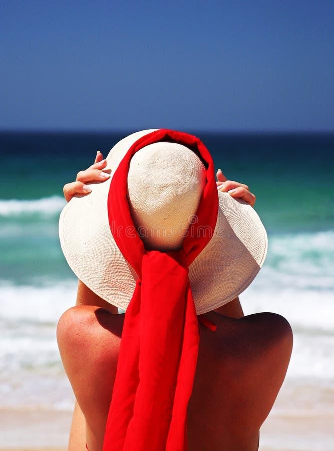 De zitting van het meisje op zandig strand in de zon het aanpassen hoed. Blauwe hemel, blauwe overzeese rode sjaal. Spanje. stock fotografie