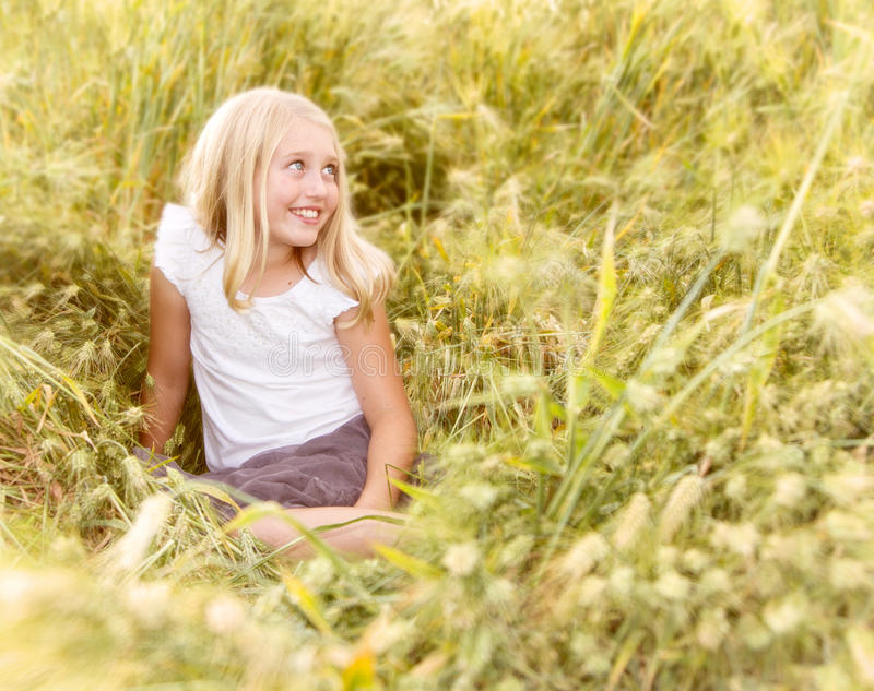 De zitting van het meisje in wheatfield stock fotografie