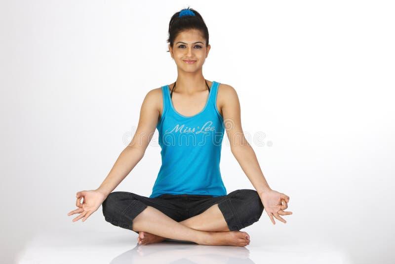 De zitting van het meisje in yoga stelt royalty-vrije stock afbeelding