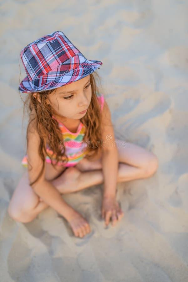 De zitting van het meisje in zand royalty-vrije stock afbeelding