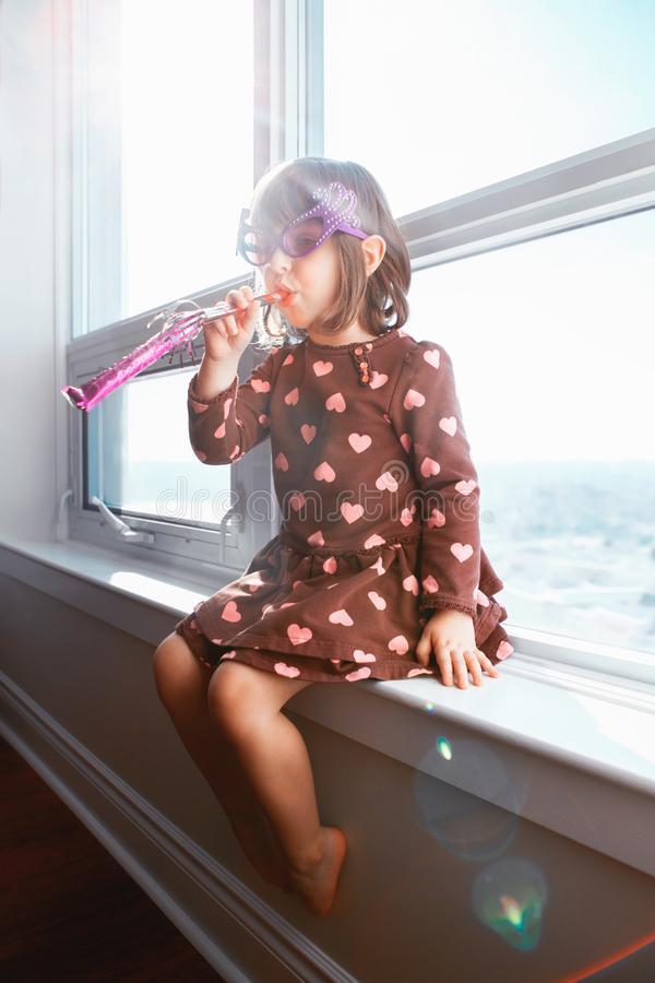De zitting van het meisjeskind op venstervensterbank thuis en het blazen fluitjetrompet het vieren verjaardag royalty-vrije stock afbeeldingen