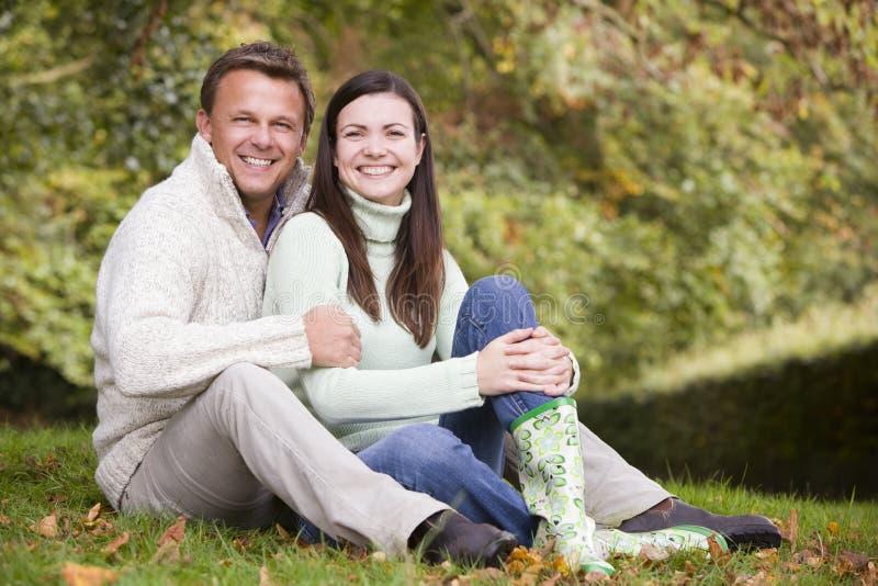 De zitting van het paar in de herfsthout stock afbeelding