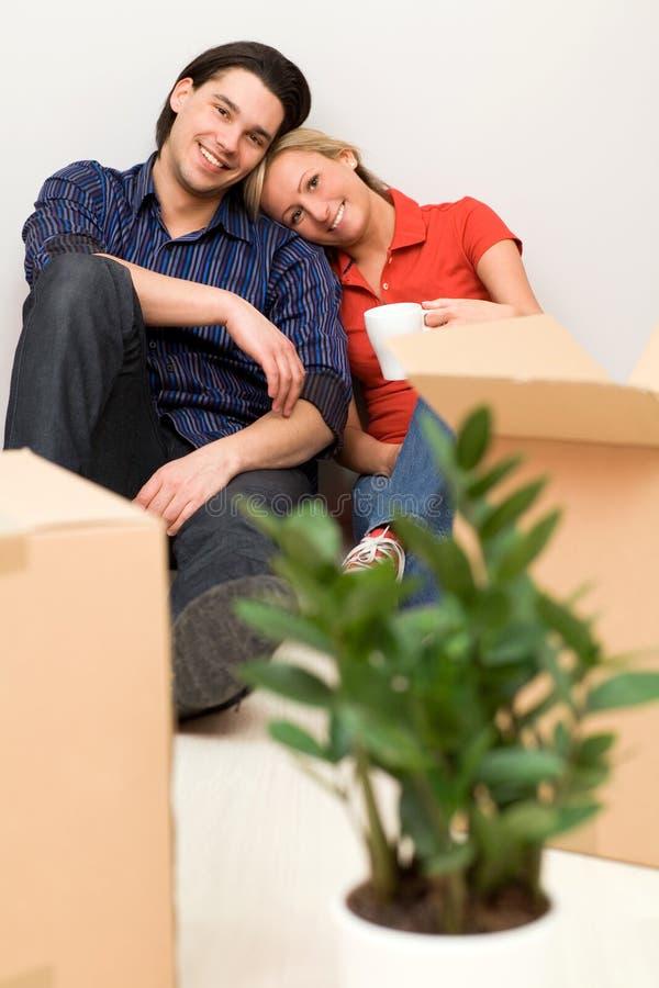 De zitting van het paar in nieuw huis royalty-vrije stock afbeeldingen