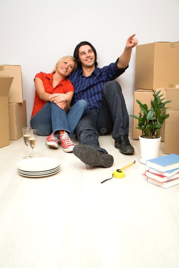 De zitting van het paar in nieuw huis stock afbeelding