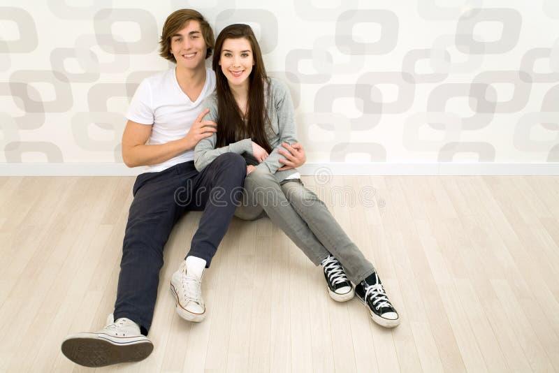 De zitting van het paar op de vloer stock foto