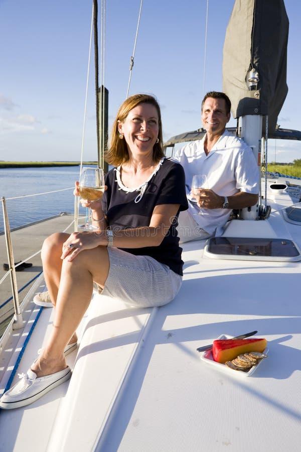 De zitting van het paar op dek van boot die van drank geniet royalty-vrije stock foto's