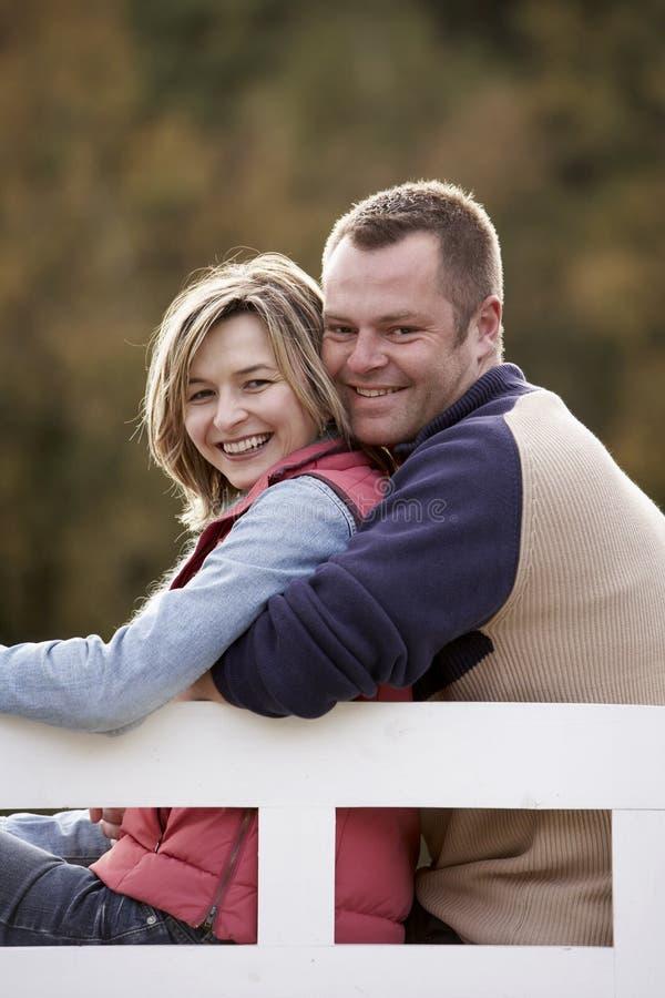 De zitting van het paar op een bank royalty-vrije stock afbeeldingen