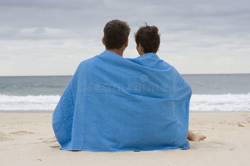 De zitting van het paar op het strand royalty-vrije stock afbeelding