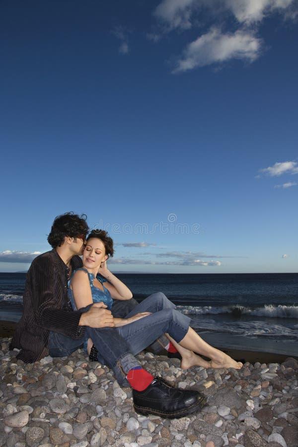 De zitting van het paar op strand. stock afbeeldingen