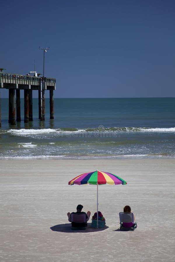 De Zitting van het paar op Strand met de Paraplu van het Strand stock afbeelding