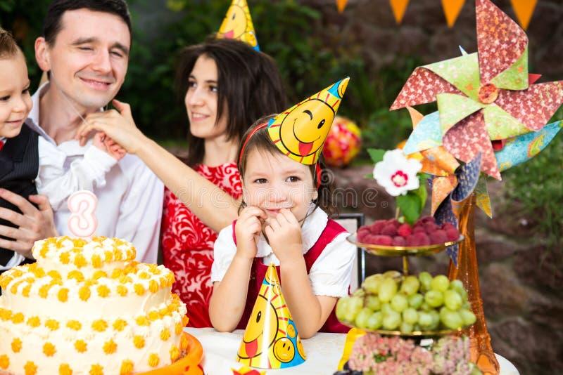 De zitting van het de partijmeisje van de kinderen` s verjaardag bij een lijst dichtbij een cake in een het feestelijke hoed en g stock afbeeldingen
