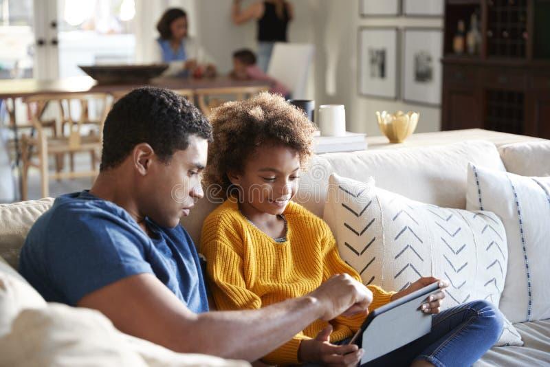 De zitting van het pre-tienermeisje op bank in de woonkamer die tabletcomputer met haar vader, moeder en peuterzitting met behulp stock afbeeldingen