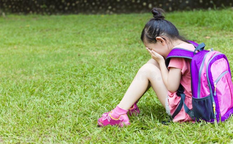 De zitting van het spanningsmeisje op het gras stock fotografie