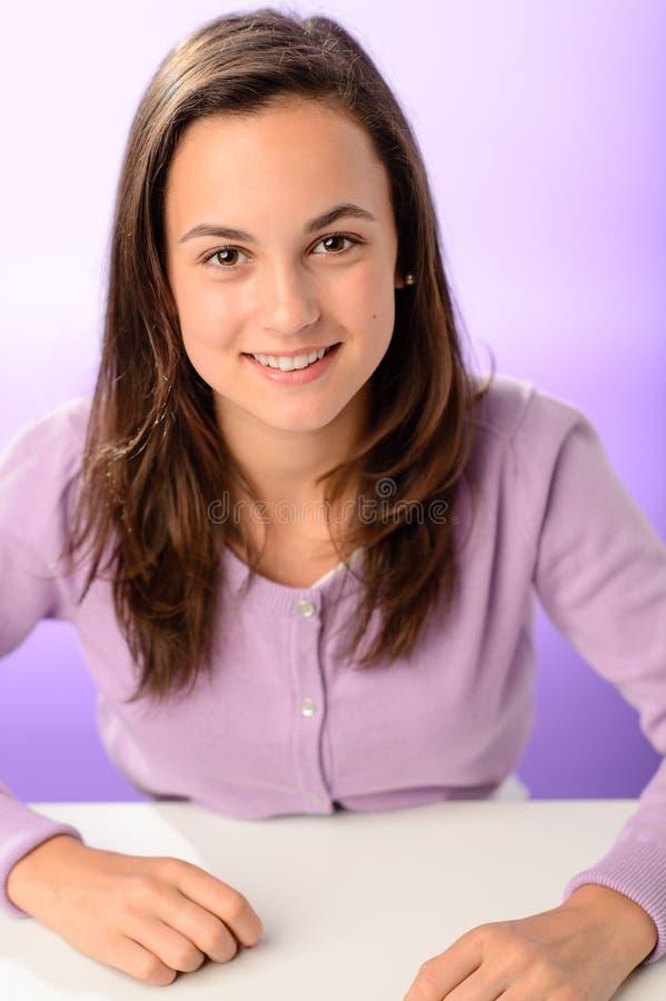 De zitting van het studentenmeisje achter bureau purper portret royalty-vrije stock fotografie