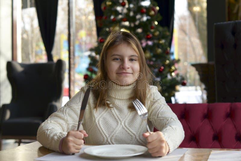 De zitting van het tienermeisje bij een lijst in een feestelijke koffie die op een heerlijk diner wachten stock foto