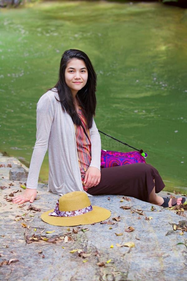 De zitting van het tienermeisje door rivier in Thailand royalty-vrije stock afbeelding