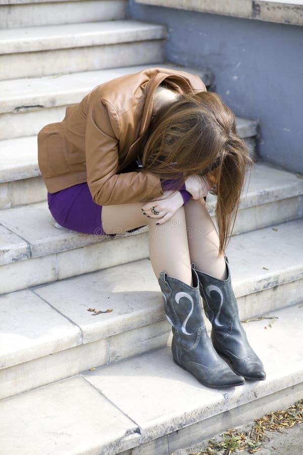 de zitting van het tienermeisje op treden stock fotografie