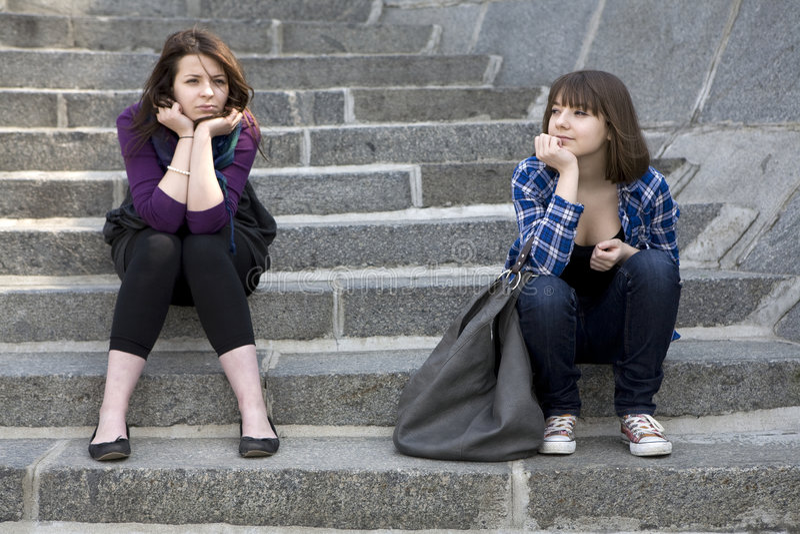 De zitting van het twee tienerjarenmeisje op treden royalty-vrije stock afbeelding