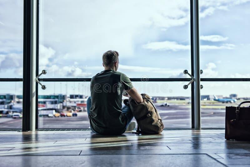 De zitting van de Hipstermens in luchthaven stock fotografie