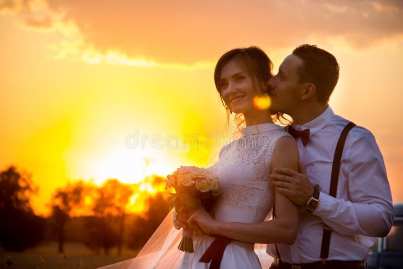 De zitting van de huwelijksfoto van de bruid en de bruidegom bij zonsondergang royalty-vrije stock foto's
