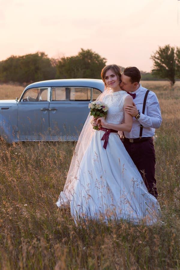 De zitting van de huwelijksfoto van de bruid en de bruidegom bij zonsondergang op het gebied stock fotografie