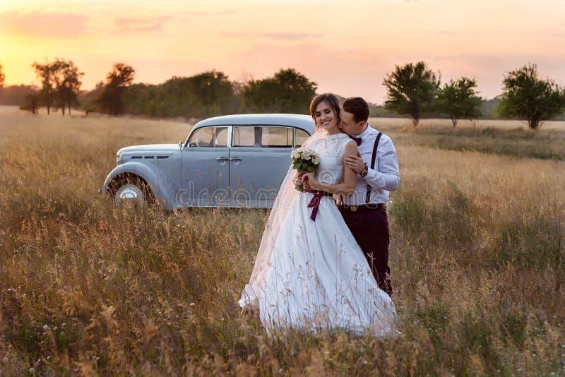 De zitting van de huwelijksfoto van de bruid en de bruidegom bij zonsondergang op het gebied royalty-vrije stock foto's