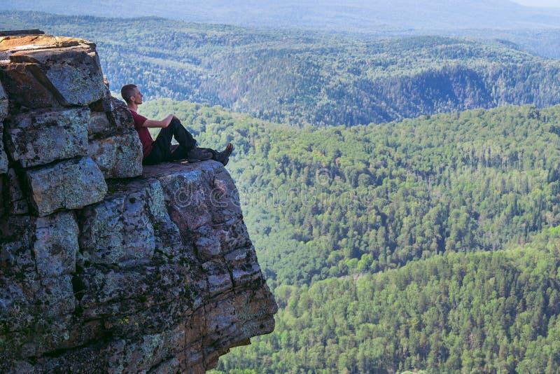 De zitting van de jonge mensenwandelaar bovenop een berg, ontspant en geniet van door toneelmening Volledige lengtespruit met exe stock afbeeldingen