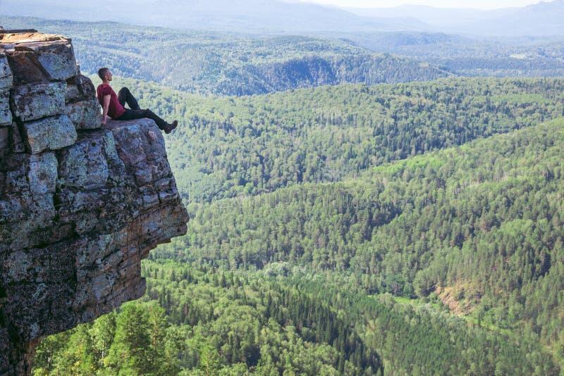 De zitting van de jonge mensenwandelaar bovenop een berg op hoge hoogte en het worden geïnspireerd door verbazende mening - Brede royalty-vrije stock foto