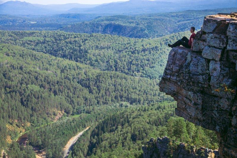 De zitting van de jonge mensenwandelaar bovenop een berg op hoge hoogte en het worden geïnspireerd door verbazende mening - Brede royalty-vrije stock afbeelding