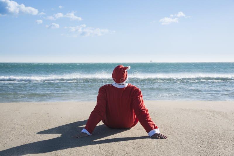 De zitting van de Kerstman op het zand van een strand stock foto