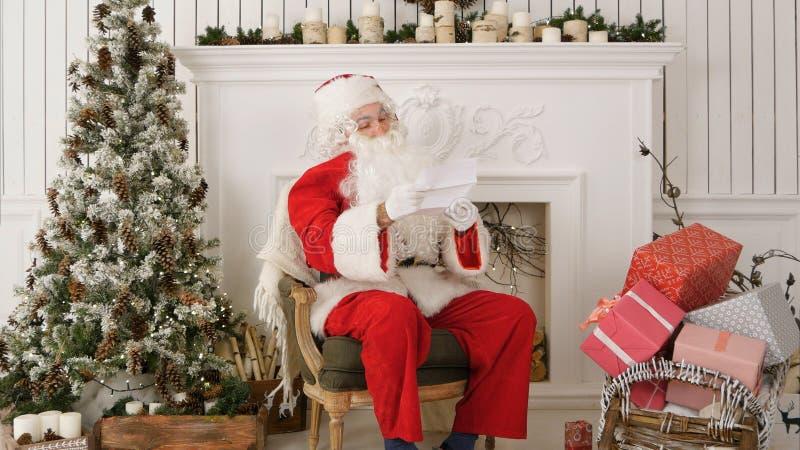 De Zitting van de Kerstman in Zijn Workshop die een brief leest Verticale Samenstelling stock fotografie