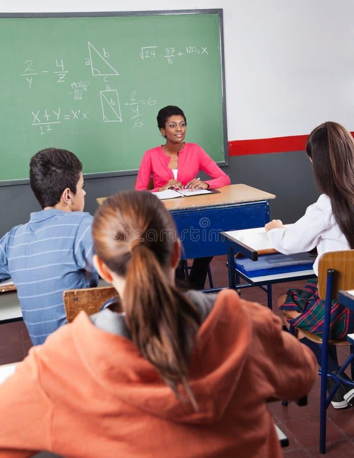 De Zitting van leraarsand teenage students in Klaslokaal royalty-vrije stock foto's