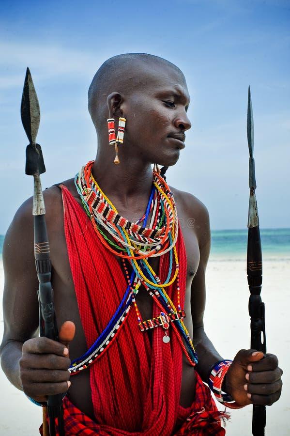 De zitting van Maasai door de oceaan stock foto