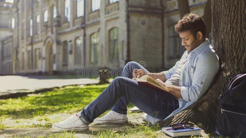 De zitting van de mengen-raskerel onder boom in park, lezingsboek, vrije tijd, hobby royalty-vrije stock foto's