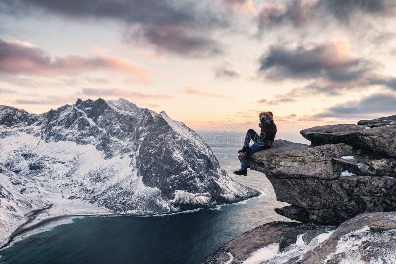 De zitting van de mensenklimmer op randrots met het sightseeing van sneeuwberg ryten onderstel stock afbeelding