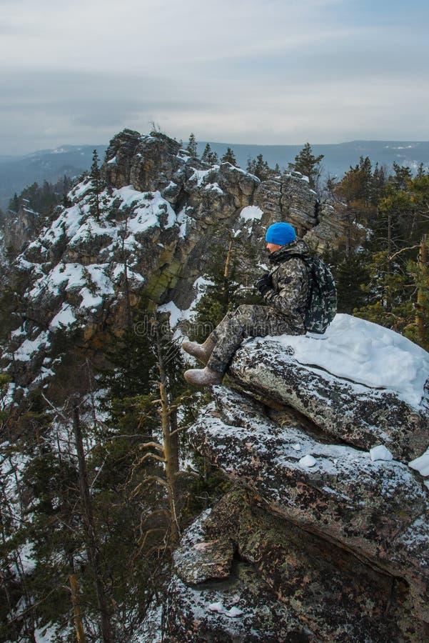 De zitting van de mensenwandelaar op rots bij bergbovenkant, de winteravontuur stock afbeeldingen