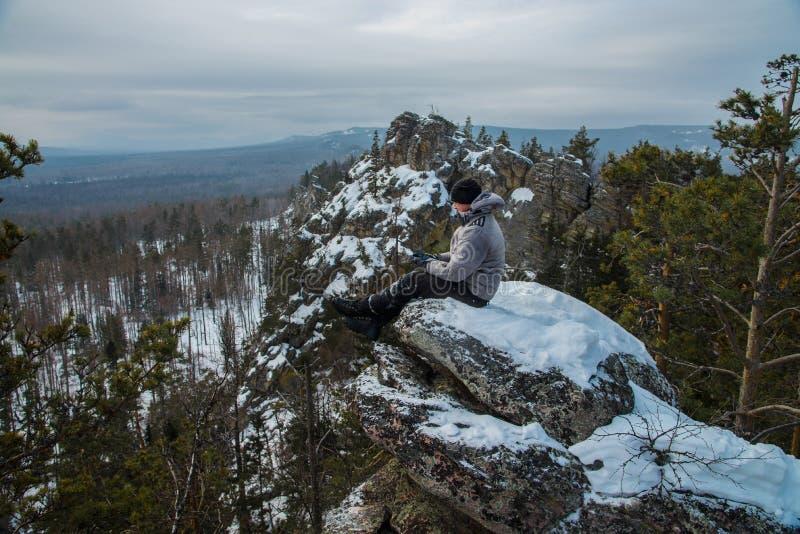 De zitting van de mensenwandelaar op rots bij bergbovenkant, de winteravontuur stock fotografie