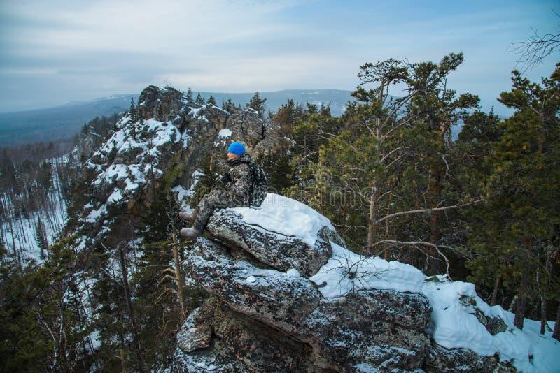 De zitting van de mensenwandelaar op rots bij bergbovenkant, de winteravontuur stock foto's
