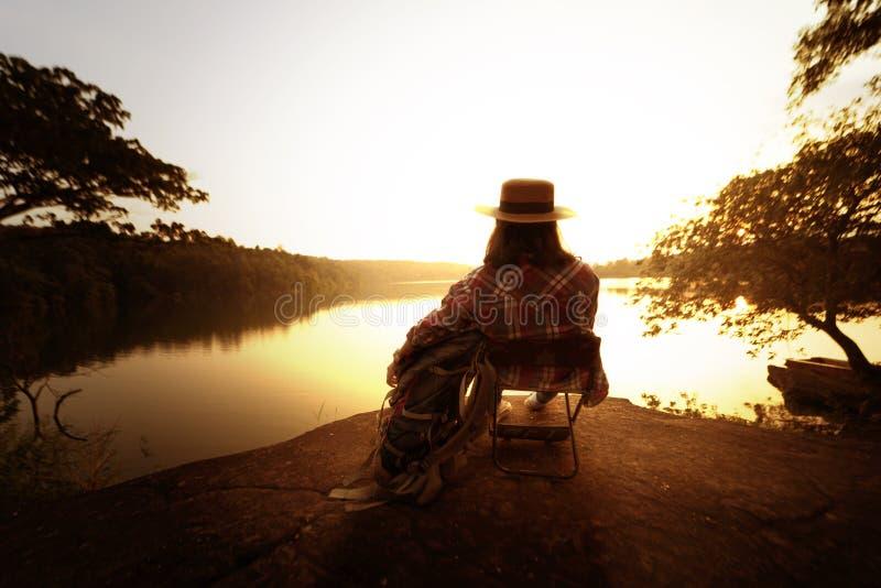 De zitting van de rugzakvrouw naast de rivier stock afbeeldingen