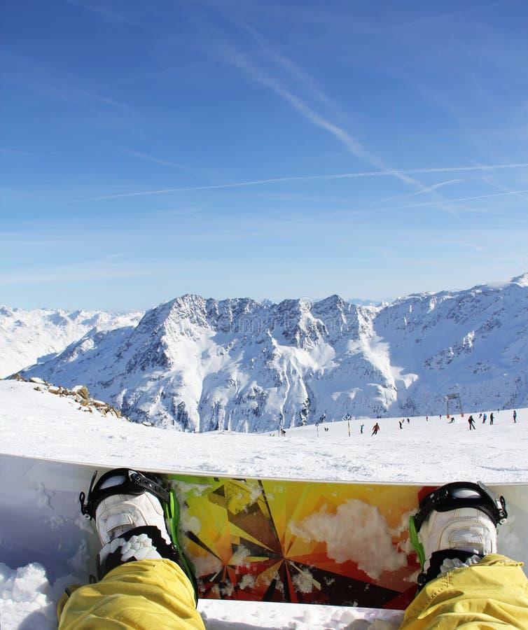 De zitting van Snowboarder op sneeuw stock foto
