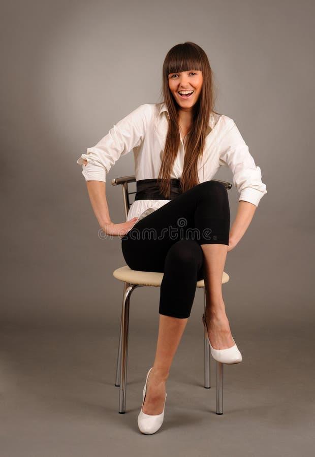 De zitting van Swoman op een stoel royalty-vrije stock afbeelding