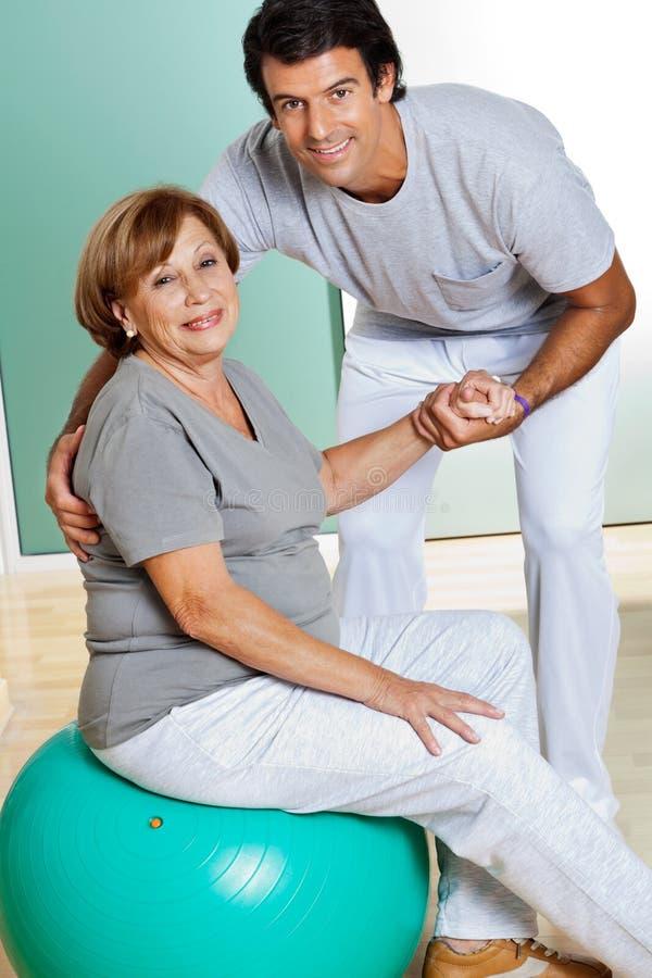 De Zitting van therapeuthelping senior woman op Geschiktheid stock afbeeldingen