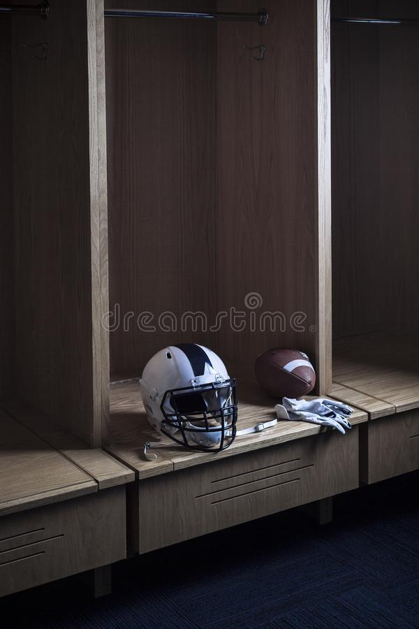 De zitting van de voetbalhelm in een Amerikaanse Voetbalkleedkamer en stock afbeeldingen