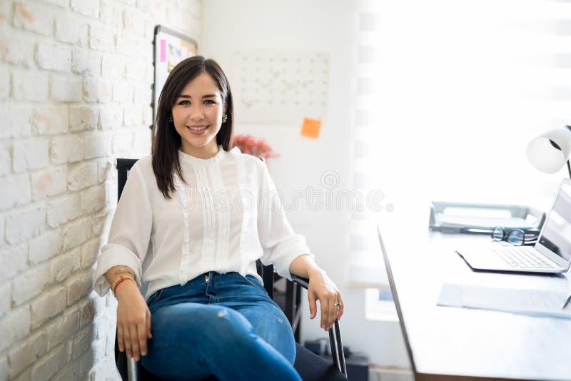De zitting van de vrouw bij haar bureau royalty-vrije stock afbeelding