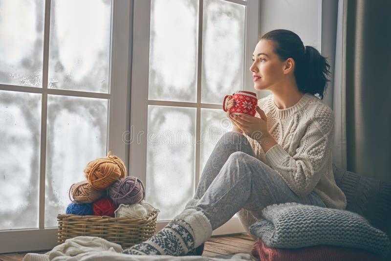 De zitting van de vrouw door het venster royalty-vrije stock fotografie