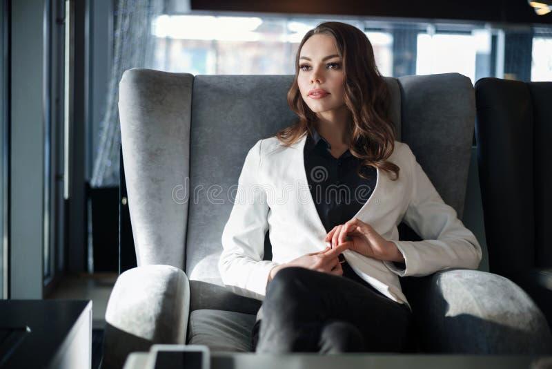 De zitting van de vrouw in een koffie Close-up op een Kop van koffie ter beschikking royalty-vrije stock afbeeldingen